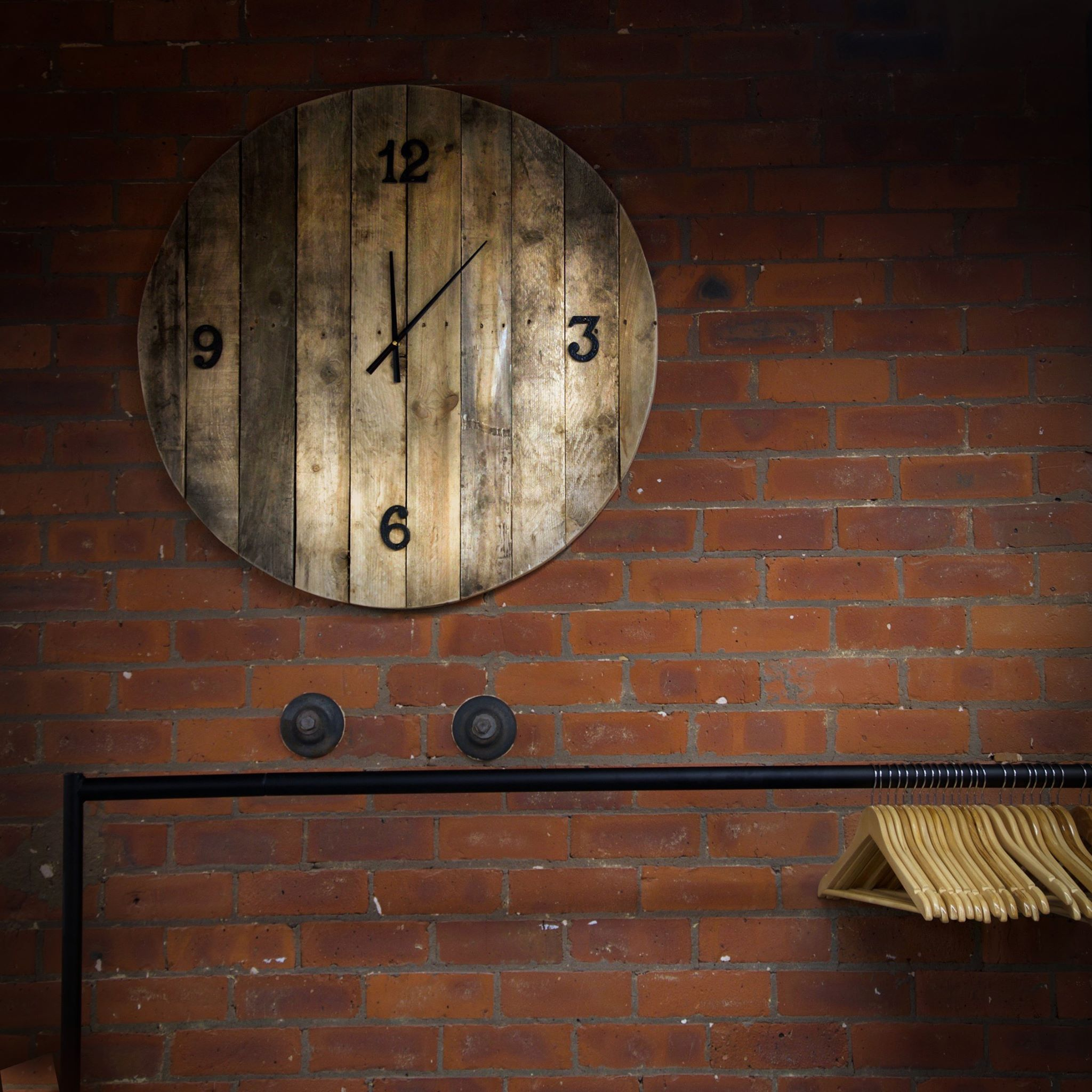 Big wooden clock on the exposed brick wall